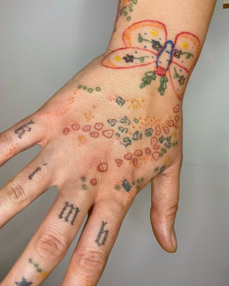 Hand tattoo piece with flowers, sprinkles and candy